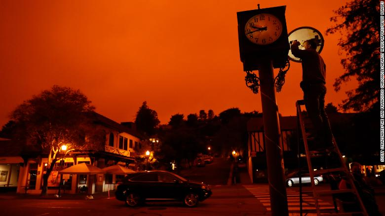 Bejhan Razi, a senior building inspector in Mill Valley, California, checks out repairs on a lamp-post clock as the sky is illuminated by nearby wildfires.