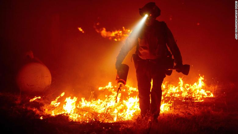 Firefighters cut defensive lines and light backfires to protect structures behind a CalFire fire station during the Bear fire, part of the North Lightning Complex fires in the Berry Creek area of unincorporated Butte County, California on September 9, 2020.