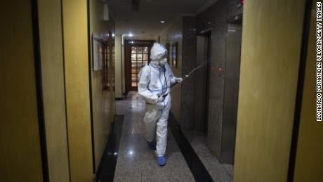 CARACAS, VENEZUELA - JULY 20: A member of the medical staff disinfects the corridors of the hotel where COVID-19 patients are staying during week 19 of radical quarantine on July 20, 2020 in Caracas, Venezuela. To manage hospital occupation rates, Venezuelan government has 4,000 hotel rooms nationwide to host and isolate patients of COVID-19 with no or mild symptoms. The Milenio hotel, in the Chaguaramas area, has 60 rooms and is now hosting 61 patients. They stay in single or double rooms with air conditioning, cable TV and internet service. Three groups of doctors rotate in shifts of three days and stay at the hotel. Patients are tested every two or three days and receive doses of Chloroquine and Azithromycin. There is international concern about the real capacity of the government of Nicolas Maduro to control the pandemic due to the health, social and economic crisis the country is going through. According to Johns Hopkins University, Venezuela has 12,334 positive cases (half of them already recovered) and 116 reported deaths. (Photo by Leonardo Fernandez Viloria/Getty Images)