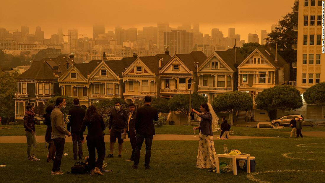 People stand in Alamo Square Park as smoke hangs over San Francisco on September 9.