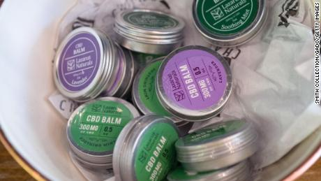Several containers of lip or skin balm containing Cannabidiol or CBD, derived from the Cannabis plant, are displayed on the shelf of a store in Walnut Creek, California.