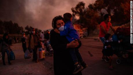 A woman carries a child after a fire broke out in the Moria migrants camp in Lesbos on September 9, 2020.