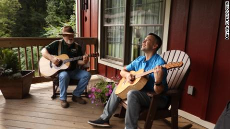 Master luthier Doug Naselroad (left) plays a tune with his mentee Earl Moore, who's holding one of 70 guitars he's made as an artist-in-residence at the Appalachian Artisan Center.