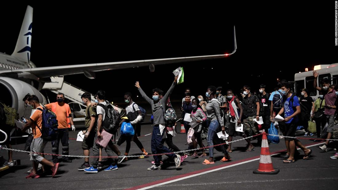 Unaccompanied minors from the Moria migrant camp board a plane on Wednesday, September 9, to be transferred to camps in northern Greece in the aftermath of the fire on Lesbos.