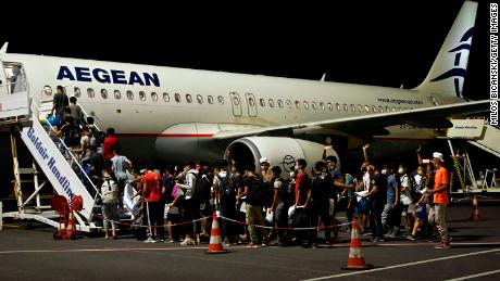 A group of children board one of three planes taking 406 unaccompanied minors from the burned camp to mainland Greece on Wednesday night.