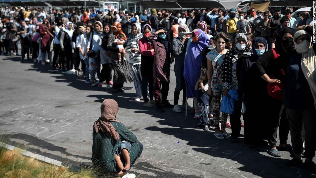 Migrants queue during a water and food distribution at a supermarket parking lot where many have taken refuge from the burned-out camp.