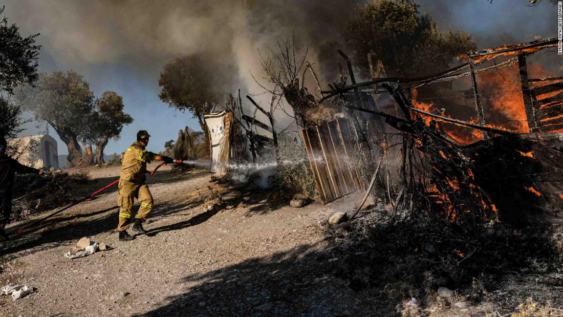 A firefighter works to put out a flame as fires continue to burn Thursday in the camp.