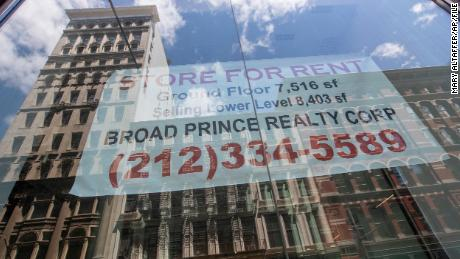 """A """"for rent"""" sign hangs in the window of an empty storefront in New York City."""