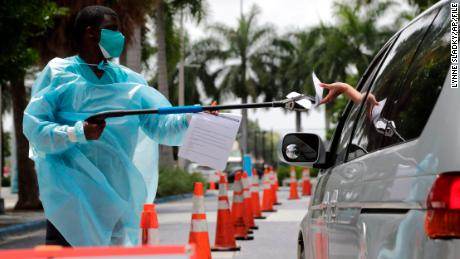 Healthcare worker Dante Hills passes paperwork to a woman in a vehicle at a COVID-19 testing site in Miami.