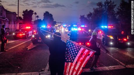 A man holds a US National flag in front of Police cars during a demonstration  in Los Angeles, California on September 5, 2020.