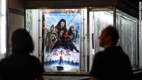 "People walk past a poster for ""Mulan"" outside a cinema in Beijing on Thursday."