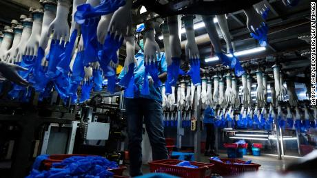 An employee monitors latex gloves on an automated production line at a Top Glove factory, February 18, 2020.