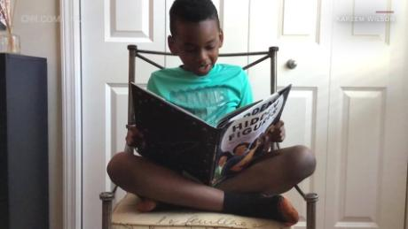 "Amir Wilson, 8, reads the book, ""Hidden Figures,"" donated to his third-grade class by the nonprofit, Young, Black & Lit."