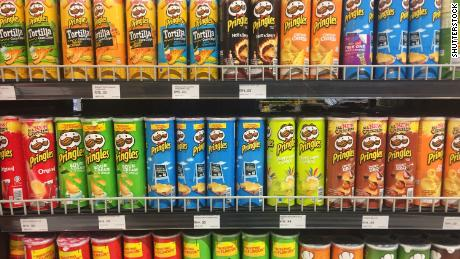 Pringles cans sit on the shelf of a grocery store.