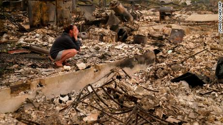 "Desiree Pierce cries Friday as she visits her home destroyed by a fire in Talent, Oregon. ""I just needed to see it, to get some closure,"" she told The Associated Press."
