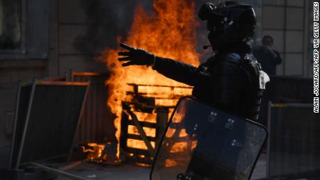 A riot police officer stands near a fire during a protest against yellow vests in Paris on September 12.