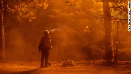 MONROVIA, CA - SEPTEMBER 11: A firefighter keeps watch on flames that could jump the Angeles Crest Highway at the Bobcat Fire in the Angeles National Forest on September 11, 2020 north of Monrovia, California. California wildfires that have already incinerated a record 2.3 million acres this year and are expected to continue till December. The Bobcat Fire has grown to more than 26,000 acres.  (Photo by David McNew/Getty Images)