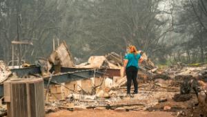 A woman surveys the damage to a home owned by her son in a mobile home park on September 11, 2020 in Ashland, Oregon. Hundreds of homes in Ashland and nearby towns have been lost due to wildfire. (Photo by David Ryder/Getty Images)