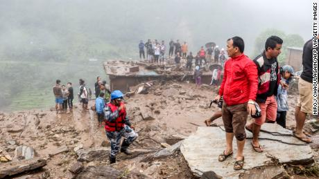 Rescue workers and residents gather for search at the scene of a landslide following heavy rains in Bahrabise municipality of Sindhupalchok district.