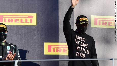 Lewis Hamilton celebrates on the podium wearing a shirt in tribute to the late Breonna Taylor.