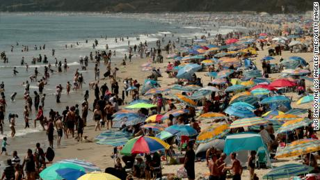 Beachgoers create a forest of umbrellas as thousands seek refuge in Santa Monica with temperatures reaching triple digits and beyond in August.