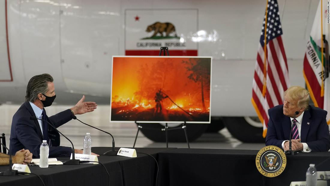 President Donald Trump listens as California Gov. Gavin Newsom speaks during a briefing about western wildfires at Sacramento McClellan Airport on Monday, September 14.