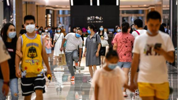 In this photo taken on September 5, 2020, people wearing face masks walk in a shopping mall in Wuhan, China