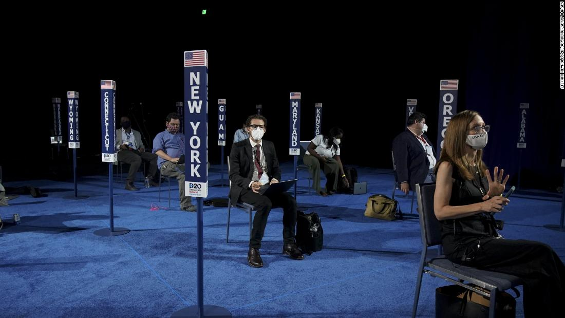Members of the media are spread out from one another before Harris' speech during the Democratic National Convention.