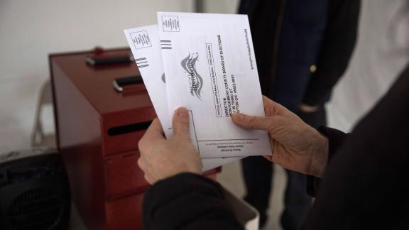 """A voter drops off an absentee ballot on March 17, 2020 in Dayton, Ohio after Ohio Primaries were canceled. - Ohio health officials ordered the state's polling stations closed for Tuesday's Democratic primary, as the governor defied a court ruling and declared a health emergency over coronavirus.""""While the polls will be closed tomorrow, Secretary of State @FrankLaRose will seek a remedy through the courts to extend voting options so that every voter who wants to vote will be granted that opportunity"""" at a later date, Governor Mike DeWine said late Monday on Twitter."""