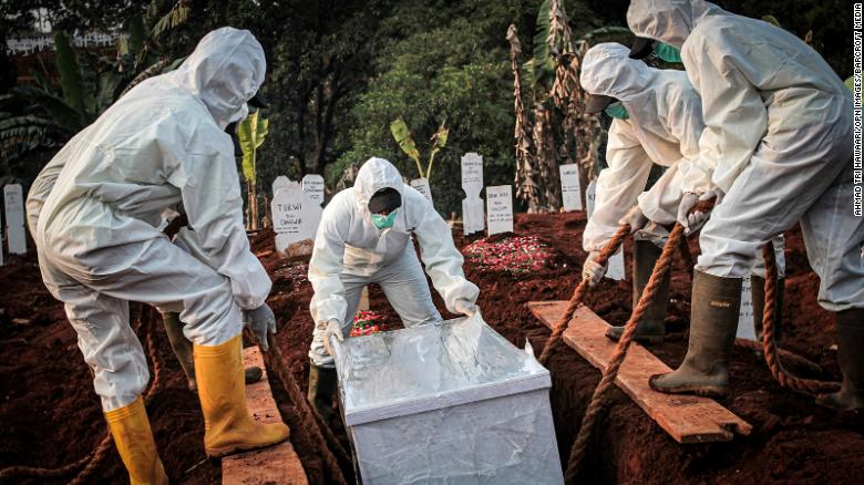 A coffin containing a coronavirus victim is buried in Indonesia's East Jakarta City.