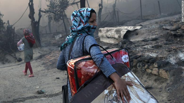 A migrant carries her belongings following the devastating blaze at the Moria camp on September 9.
