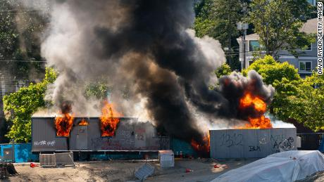 Trailers on a construction site for a youth detention center burn after protesters targeted them during protests in Seattle on July 25. (Editor's note: Part of this photo has been blurred because of profanity.)