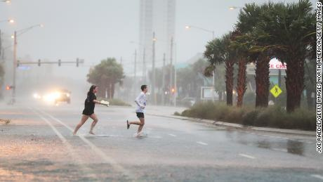 GULF SHORES, ALABAMA - SEPTEMBER 15: People run across a road through the rain and wind as the outer bands of Hurricane Sally come ashore on September 15, 2020 in Gulf Shores, Alabama. The storm is bringing heavy rain, high winds and a dangerous storm surge from Louisiana to Florida. (Photo by Joe Raedle/Getty Images)