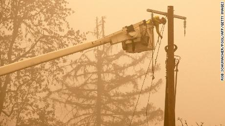 Workers continue to repair the power system after flames from the Beachie Creek Fire burned through Fishermen's Bend Recreation Site in Mill City, Oregon.