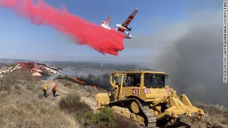 A bulldozer digs a fire mine while a Cal Fire plane does a phos check near a 110 acre fire at Vandenberg Air Force Base.