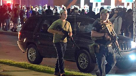 Kyle Rittenhouse, left, with backwards cap, in Kenosha, Wisconsin, on August 25, 2020. Prosecutors have charged Rittenhouse, 17, in the fatal shooting of two protesters and the wounding of a third in Kenosha during a night of unrest following the police shooting of Jacob Blake.