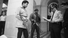 Two members of the Black Panther Party are met on the steps of the State Capitol in Sacramento, California, on May 2, 1967. Police Lt. Ernest Holloway informed them they would be allowed to keep their weapons as long as they caused no trouble.
