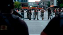 Supporters of the NFAC, an all-Black armed group, face off against the Three Percenters, an armed far-right group -- separated by police barricades -- at a protest against the killing of Breonna Taylor in Louisville, Kentucky, on July 25.