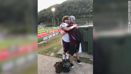 Scott Sullivan, terminally ill with cancer, hugs his son Cade before the opening game of high school football season.