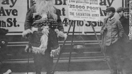 A man dressed as Santa Claus advertises a free Christmas dinner organized by the Salvation Army in New York, around 1910.