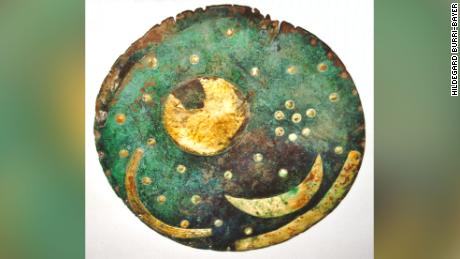 This image shows the Nebra sky disc in 2002. The disc includes a crescent moon as well as other cosmic features and depicts an abstract representation of a starry night.
