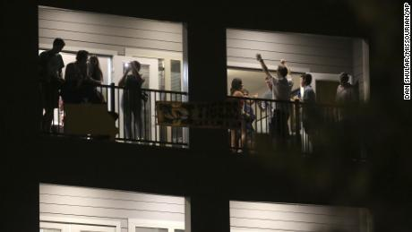Partiers congregate on the balcony of a downtown apartment in Columbia, Mo., near the University of Missouri campus.