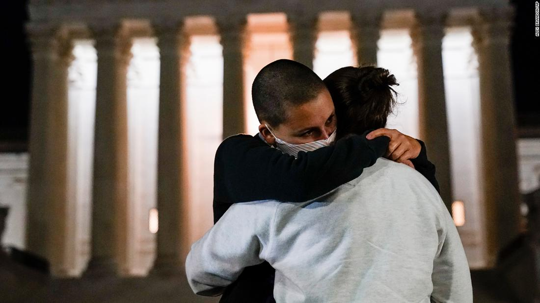 A couple hugs outside the Supreme Court on September 18 in Washington.