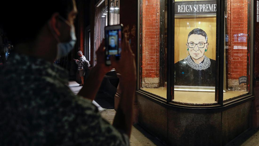 A person pauses to photograph a painting in a Manhattan storefront on Broadway of Supreme Court Justice Ruth Bader Ginsburg, who passed away on Friday, September 18.