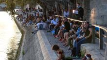 People gather along the Seine river bank during sunset in Paris, on Thursday, amid the resurgence of the coronavirus.