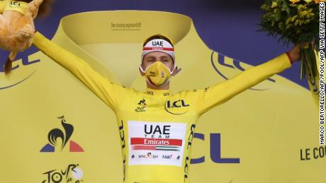 Tadej Pogacar proudly dons the yellow jersey on the podium after winning the 20th stage of the 107th edition of the Tour de France.