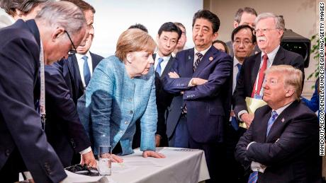 German Chancellor Angela Merkel deliberates with US president Donald Trump on the sidelines of the official agenda of the G7 summit on June 9, 2018 in Charlevoix, Canada.