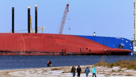 People walk the beach near the Golden Ray cargo ship on February 27, 2020, in Jekyll Island, Georgia. The vessel capsized in St. Simons Sound in 2019. Plans to cut it into segments and lift it out of the water have been on hold because of coronavirus.
