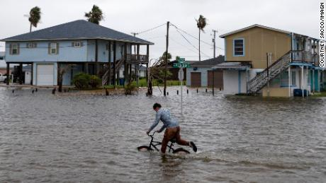A boy rides a bike on a flooded street in Rockport, Texas, as Tropical Storm Beta approaches Monday.