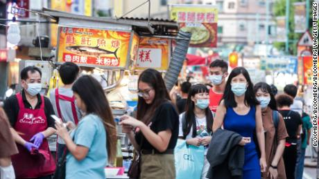 People wearing protective masks walk past food stalls at the Ningxia Night Market in Taipei, Taiwan, on July 30, 2020.